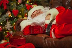 Santa Clause snoozing in a decorated living room with sack full stock photos
