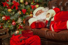 Santa Clause snoozing in a decorated living room with sack full royalty free stock photos