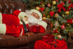Santa Clause snoozing in a decorated living room with sack full stock photography