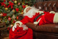 Santa Clause snoozing in a decorated living room with sack full royalty free stock photo