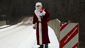 Santa Clause try to stop car on the bridge stock video footage