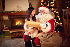 Santa Clause with young girl in lap reading Christmas whishes. From long paper Royalty Free Stock Photo