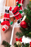 Santa Clauses clamber up sexy legs Royalty Free Stock Photos