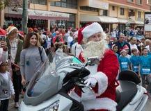 Santa Clauses en un paseo de la vespa de motor entre los participantes y los visitantes del ` anual Cristmas de la raza corren el Fotos de archivo