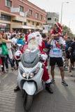 Santa Clauses en un paseo de la vespa de motor entre los participantes y los visitantes del ` anual Cristmas de la raza corren el Imagen de archivo