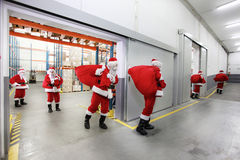 Santa clauses leaving a gift distribution center Stock Photo
