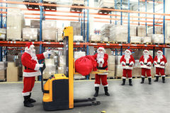 Santa clauses in line for sacks of gifts
