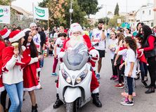 Santa Clauses on a motor scooter ride among the participants and visitors of the annual race `Cristmas Run` in Mi`ilya in Israel Royalty Free Stock Image