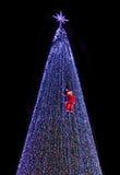 Santa climb on christmas tree Stock Photo