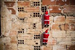 Santa climbing a grunge wall royalty free stock photo