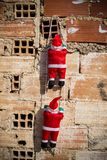 Santa climbing a grunge wall stock photography