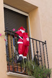 Santa climbing into a house Royalty Free Stock Photo