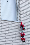 Santa climbing into a house Royalty Free Stock Photos