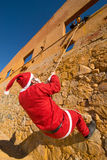 Santa climbing. A wall while a scary Halloween monster is waiting for him Royalty Free Stock Image