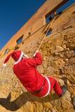 Santa climbing Royalty Free Stock Image