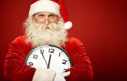 Santa with clock. Photo of happy Santa holding clock showing five minutes to midnight Stock Images