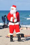 Santa Claus on a beach walking. In South Miami in December royalty free stock photo