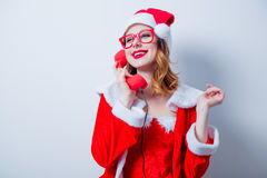 Santa Clous girl with eyeglasses and handset Royalty Free Stock Photos