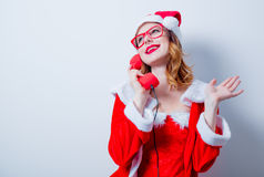 Santa Clous girl with eyeglasses and handset Royalty Free Stock Photography