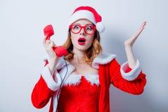Santa Clous girl with eyeglasses and handset Royalty Free Stock Photo