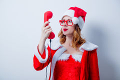 Santa Clous girl with eyeglasses and handset Royalty Free Stock Images