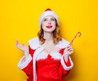Santa Clous girl in red clothes with candy. Portrait of Young Santa Clous girl in red clothes with candy on yellow background Royalty Free Stock Photography