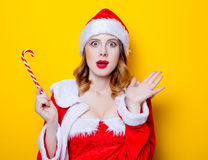 Santa Clous girl in red clothes with candy. Portrait of Young Santa Clous girl in red clothes with candy on yellow background Royalty Free Stock Photos