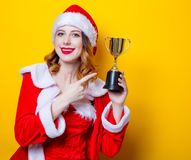 Santa Clous girl in red clothes with trophy prize. Portrait of Young Santa Clous girl in red clothes with trophy prize on yellow background Stock Images