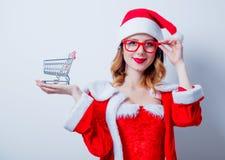 Santa Clous girl with shopping cart Royalty Free Stock Image