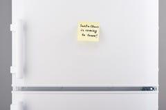 Santa Clouse está viniendo a la nota de la ciudad sobre el refrigerador blanco Imágenes de archivo libres de regalías