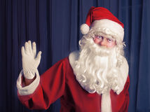 Santa Clouse greeting over the  dark curtain Royalty Free Stock Image