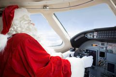 Santa In Cockpit Flying Private Jet. Man in Santa costume holding control wheel in cockpit of private jet Royalty Free Stock Photos