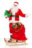 Santa com o saco de brinquedos e de pequeno trenó isolados Fotografia de Stock Royalty Free
