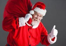 Santa com o saco do presente que mostra os polegares acima Foto de Stock