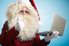 Santa com os dispositivos nas mãos imagens de stock royalty free