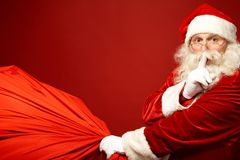 Santa coming. Portrait of Santa Claus with huge red sack keeping forefinger by his mouth and looking at camera Stock Photo