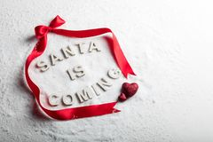 SANTA IS COMING text and red ribbon royalty free stock photo
