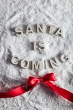SANTA IS COMING writing and a red bow stock images