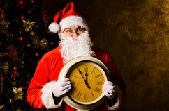 Santa con el reloj Foto de archivo libre de regalías