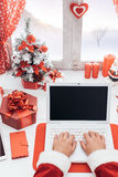 Santa connecting with a laptop Stock Images