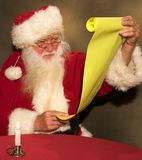Santa contrôlant sa liste Photographie stock