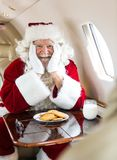 Santa With Cookies And Milk Sitting In Private Jet. Portrait of happy man in santa costume with beard pulled down Stock Photography