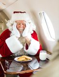 Santa With Cookies And Milk Sleeping In Private. Man in Santa costume with cookies and milk sleeping in private jet Royalty Free Stock Photos