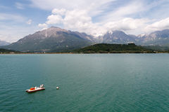 Santa Croce Lake. The Dolomites Mountains behind and a boat. The city near the mountains is Alpago, Belluno province, Italy Royalty Free Stock Photography