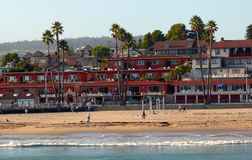 Santa Cruz beach. With people enjoying the sun and ocean. Palm trees and motels on the hill Stock Image