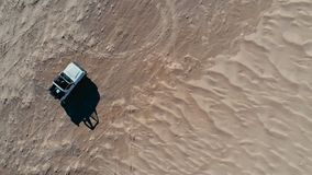 aerial picture of a desert sand dune with a 4x4 approaching from the top down stock photography