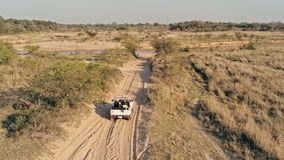 aerial picture of a desert steppe landscape with a 4x4 car approaching a small river stream royalty free stock photo
