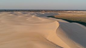 Aerial picture of young people standing on the peak of a sand dune in beautiful desert environment. Santa Cruz, Bolivia - SEPT 5 2018: aerial picture of young stock photography