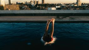 Young man jumping to the rooftop pool above the city. Santa Cruz, Bolivia - SEPT 5 2018: young man jumping to the rooftop pool above the city stock images