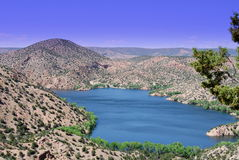 Santa Cruz lake. With green brush , trees, blue skies with clouds, and hills Stock Images